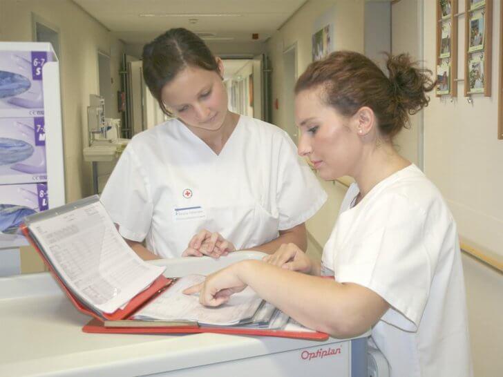 Krankenpflege-Schülerinnen bei Akten sichten